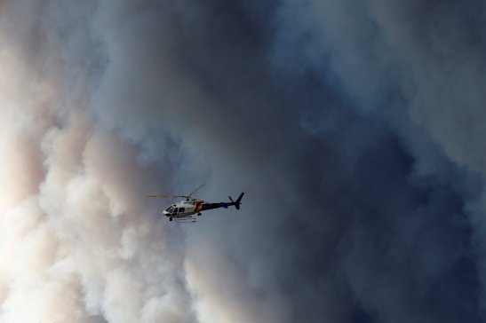 A helicopter flies past smoke from wildfires near Fort McMurray, Alberta, Canada, May 6, 2016.