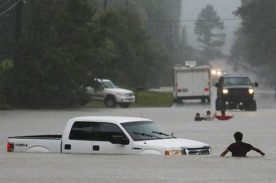 A man, foreground, checks to make sure everyone made it safely out of a truck that flooded when the three men in the background drove around a closed road barrier and lost control of the vehicle in rising flood water on May 27, 2016, in Magnolia, Texas. Michael Ciaglo / AP