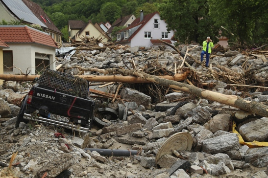 BRAUNSBACH, GERMANY - MAY 30:  A man stands among boulders, smashed trees and cars and other debris that cover a street in the village center following a furious flash flood the night before on May 30, 2016 in Braunsbach, Germany. The flood tore through Braunsbach, crushing cars, ripping corners of houses and flooding homes during a storm that hit southwestern Germany. Miraculously no one in Braunsbach was killed, though three people died as a result of the storm in other parts of the country.  (Photo by Sean Gallup/Getty Images)