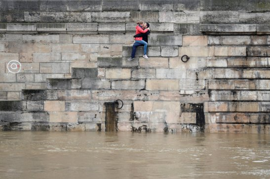 A couple exchanges kisses on the bank as high waters causes flooding along the Seine River in Paris, France, June 1, 2016.  REUTERS/Charles Platiau