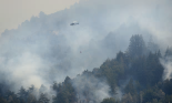 A helicopter flies in to make a water drop while fighting a wildfire on a ridge above Rancho San Carlos in Carmel Valley, California, on Saturday. Photograph: David Royal/AP