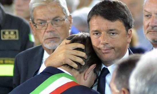 Italian prime minister Matteo Renzi embraces the mayor of Arquata del Tronto, Aleandro Petrucci, during the mass funeral in Ascoli Piceno. Photograph: Cristiano Chiodi/EPA