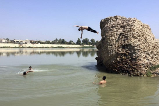Iraqis jump off the ruins of an old building into the Tigris River to beat the heat in Baghdad on Aug. 1. The temperature in Baghdad reached 117 degrees. (Ali Abdul Hassan/AP)