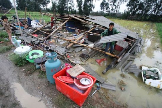 Photo: Collecting what remains of his belongings, this Jinjiang resident cleans up after Typhoon Meranti. (Reuters: China Daily )