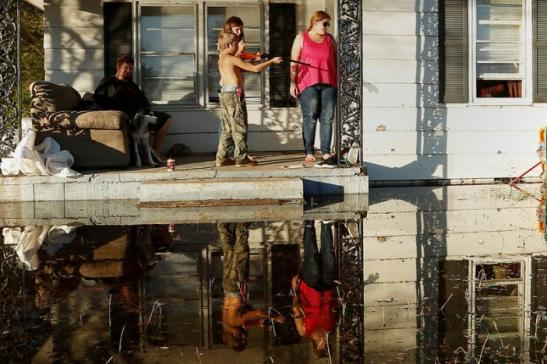 Local residents gather on their front porch as a child shoots a BB gun while they seek refuge from flood waters due to Hurricane Matthew in Lumberton, North Carolina, October 12, 2016. REUTERS/Carlo Allegri