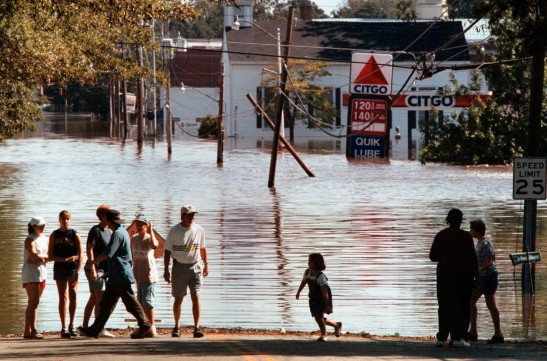 Residents of Tarboro, N.C., stop at a downtown intersection to marvel at how the rising Tar River took over their town in September 1999. (Dudley M. Brooks/ The Washington Post)
