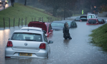 A resident passes submerged cars in Hartcliffe. Photograph: Matt Cardy/Getty Images