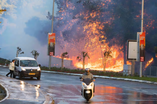 People drive past a fire in the northern Israeli port city of Haifa. Photograph: Jack Guez/AFP/Getty Images