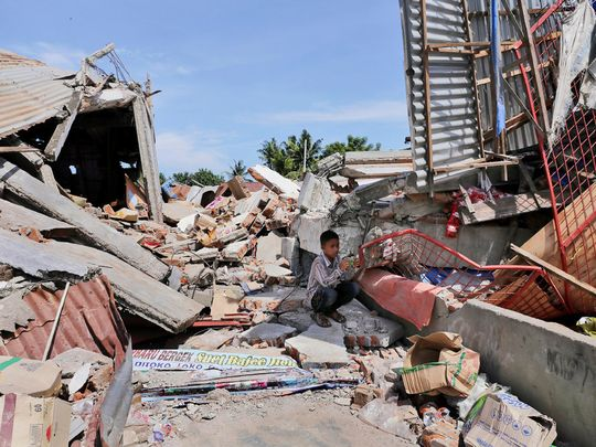 A boy sits on the rubble of a building that collapsed after an earthquake in Pidie Jaya, Aceh province, Indonesia, on Dec. 7. (Photo: AP)