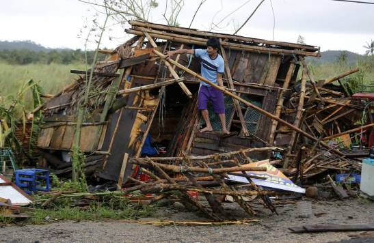 A villager works on a damaged home in the town of Pamplona, Camarines Sur, on Monday. Photo: European Pressphoto Agency