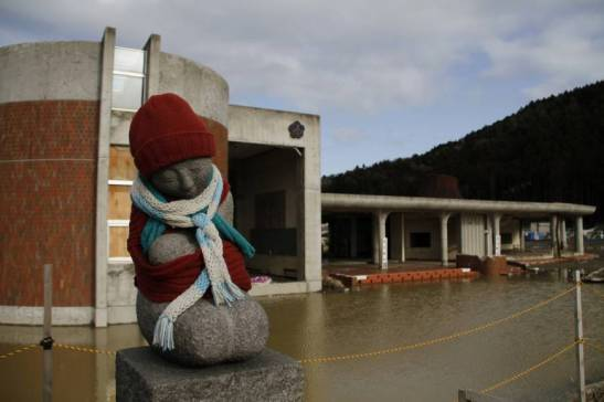 A stone statue stands near tsunami-hit Okawa Elementary School in Ishinomaki, Miyagi Prefecture, in March 2012. The education ministry plans to make classes on disaster response a mandatory subject for university students aiming to become teachers. | AP