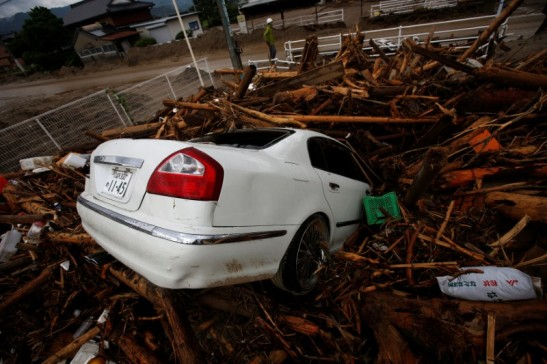 Debris and a car which were swept by heavy rain are seen in Asakura