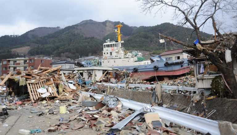 US_Navy_110315-N-2653B-148_A_tug_boat_is_among_debris_in_Ofunato_Japan_following_a_9.0_magnitude_earthquake_and_subsequent_tsunami-e15253