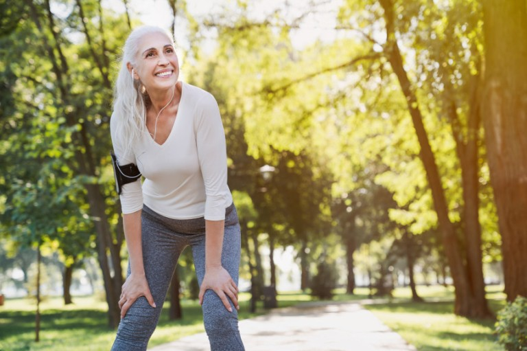 Portrait of athletic mature woman resting after jogging outdoors at park