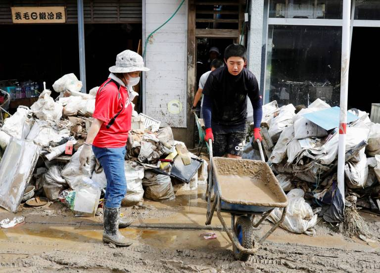 People clear debris from damaged shops after floods caused by torrential rain in Hitoyoshi, Kumamoto Prefecture